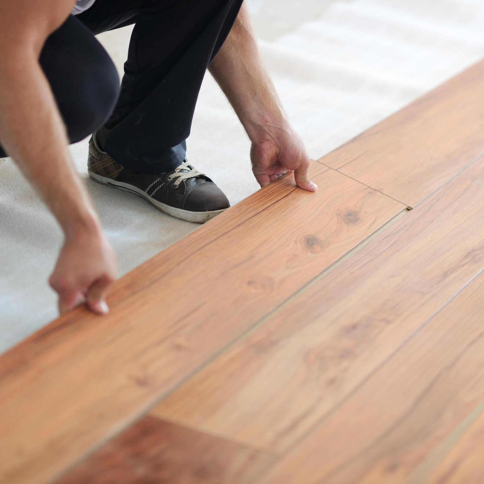 Man installing laminate flooring | Frazee Carpet & Flooring